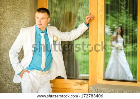 bride and groom near the window looking into the reflection