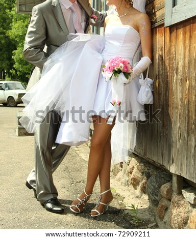 Bride and groom near the wooden house. - stock photo