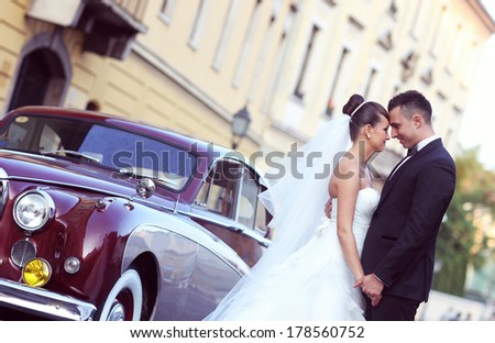 Bride and groom near vintage car - stock photo