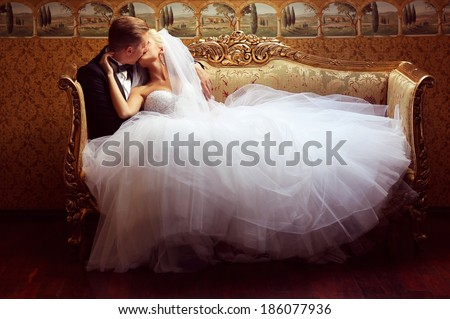 Bride and groom on a luxury hotel, kissing on a sofa - stock photo