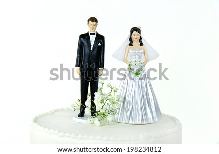 bride and groom on a wedding cake tier isolated on white - stock photo