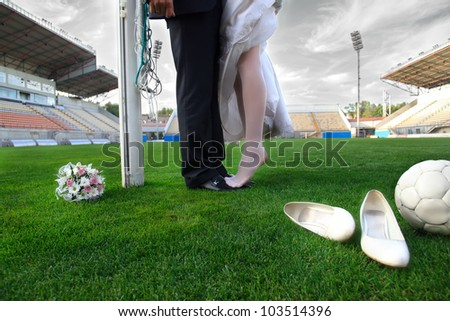 Bride and groom on football stadium with soccer ball - stock photo