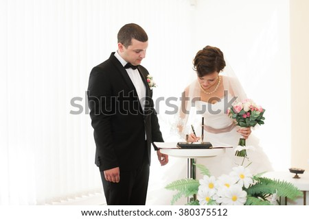 Bride and groom on marriage registration. The groom looks at the bride. Newlyweds at the wedding ceremony.