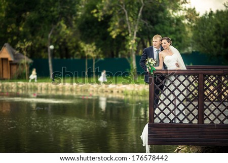 Bride and groom on the banks of the romantic lake. - stock photo