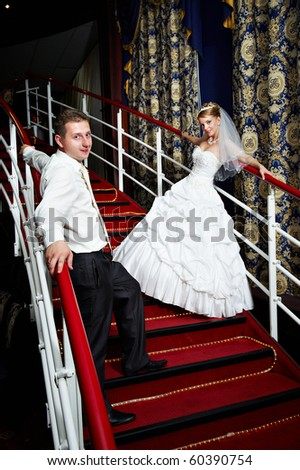 Bride and groom on the red stairs on banquet - stock photo