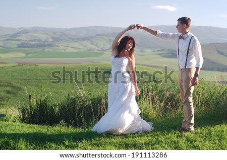 Bride and groom outside garden wedding with African Natal Midlands mountain scenery background - stock photo