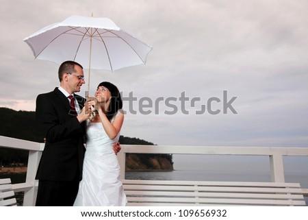 bride and groom, pier cloudy dusk sky. - stock photo