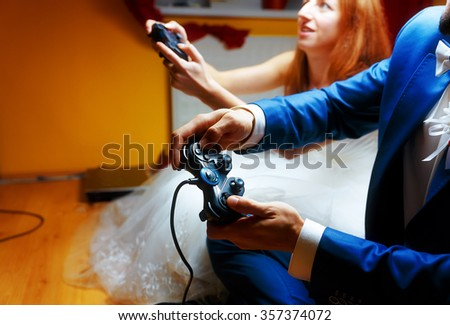 bride and groom playing together videogames with joysticks - gaming and wedding concept