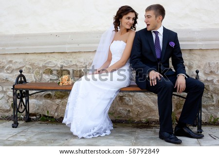 Bride and groom posing and smiling - stock photo