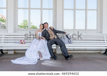 Bride and groom resting on a bench / wedding / bridal couple