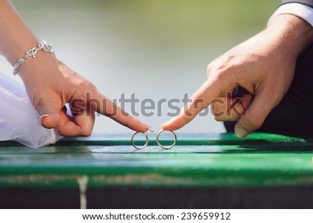 bride and groom rolling wedding rings - stock photo