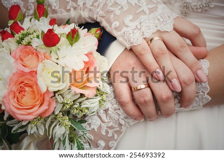 Bride and groom's hands with wedding bouquet and rings - stock photo