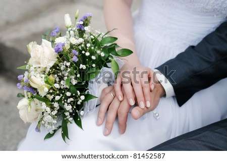 Bride and groom's hands with wedding rings - stock photo