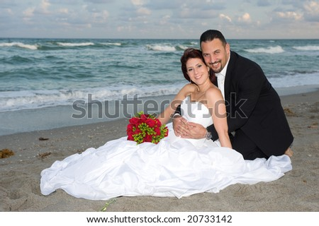 Bride and Groom Sitting at the Beach - stock photo