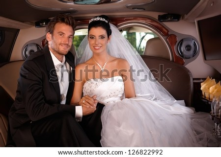 Bride and groom sitting happily in limo on wedding-day. - stock photo