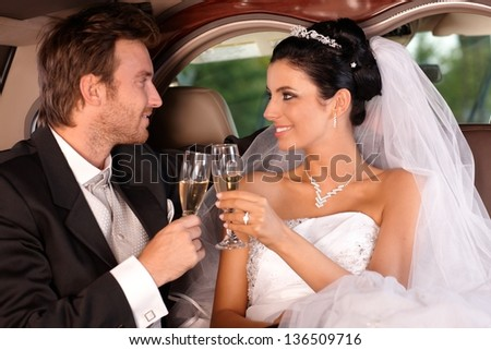 Bride and groom sitting in limousine, clinking glasses on wedding-day. - stock photo