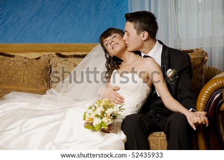bride and groom sitting in the lobby of the hotel. He hugs and kisses the bride on her cheek. She's smiling with happiness. in the hands of the bride holding a bouquet  - stock photo