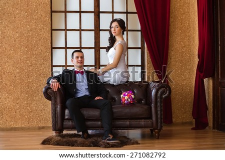 Bride and groom sitting on a leather sofa in the loft - stock photo