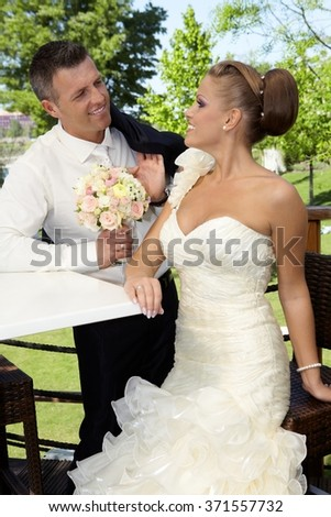 Bride and groom smiling happy outdoors on wedding-day, bride sitting on chair, groom leaning to table. - stock photo