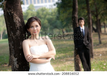 Bride and groom stand in the garden - stock photo