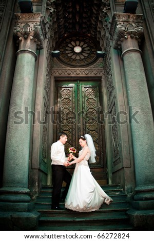bride and groom standing near beautiful building