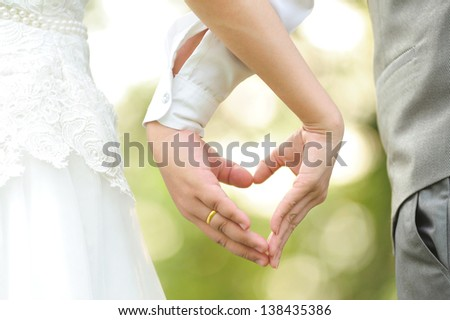 Bride and groom standing together with heart - stock photo