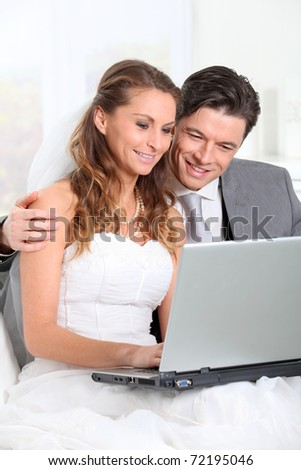 Bride and groom surfing on internet - stock photo