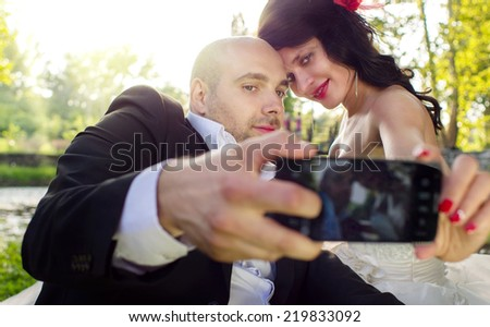 Bride and groom taking a selfie with a smart phone - stock photo