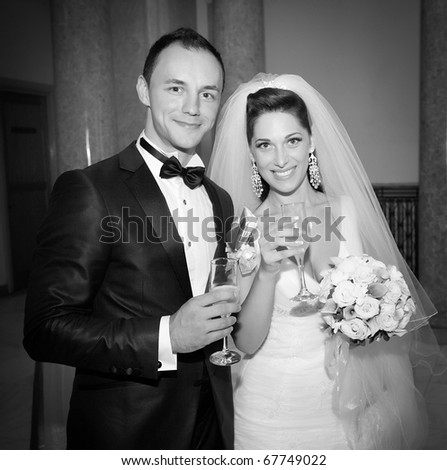 Bride and groom together with glasses - stock photo