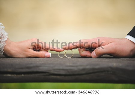 bride and groom touching rings by finger - stock photo