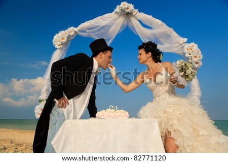 Bride and Groom Under Archway on Beach with wedding cake. Bride giving a bit of cake to groom - stock photo