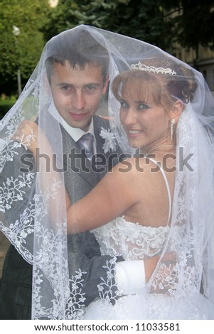 bride and groom under the veil looking at camera