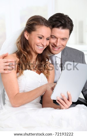 Bride and groom using electronic tablet - stock photo