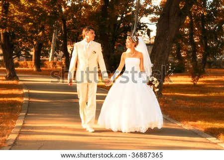 Bride and Groom walking in autumn - stock photo