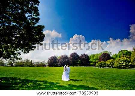 Bride and groom walking in the park - stock photo