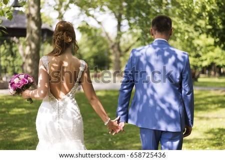 bride and groom walking in the park and holding each other for hands