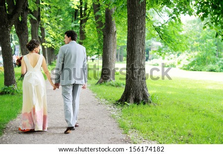 Bride and groom walking together in a park