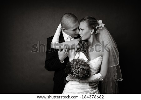Bride and groom wedding photo taken in the studio on a black background - stock photo