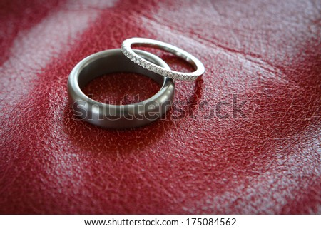 bride and groom wedding rings on red background - stock photo