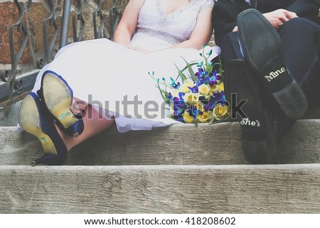 """Bride and groom with bottom of shoes that read """"I do"""" and """"She's mine"""". - stock photo"""