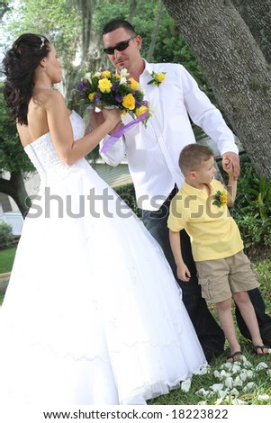 bride and groom with child - stock photo