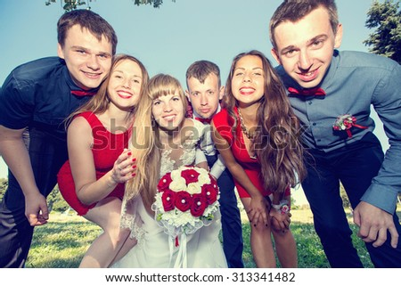 Bride and groom with friends. Just married. Group of young friends make selfie photo with smart phone camera in wedding day. Funny happy young people on the park. Wedding group of friends. Toned image - stock photo