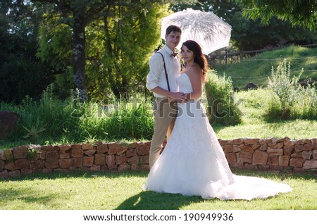 Bride and groom with parasol outside garden wedding ceremony - stock photo