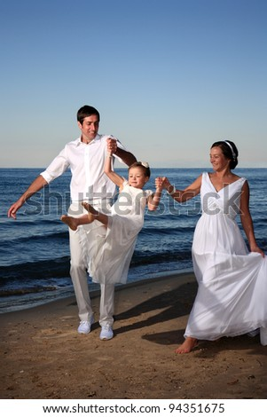 bride and groom with their kid at the beach