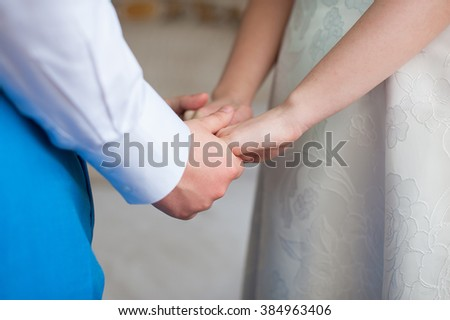 Bride and groom with wedding dress and suit, holding hands, mid section, side view. indoor.