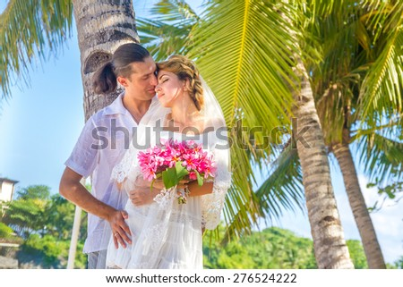 bride and groom, young loving couple, on their wedding day, outdoor beach wedding on tropical beach and sea background - stock photo