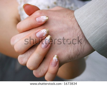 Bride and her groom's hands during the wedding.
