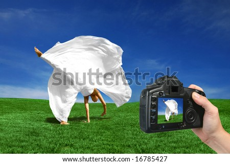 Bride Being Photographed Cartwheeling in the Grass by a Digital Camera - stock photo
