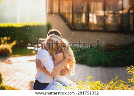 Bride blonde sensually embraces the bride in the magical light of sunset, wedding, love, couple, lifestyle - stock photo