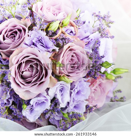 bride bouquet of purple flowers  with wedding gold rings - stock photo